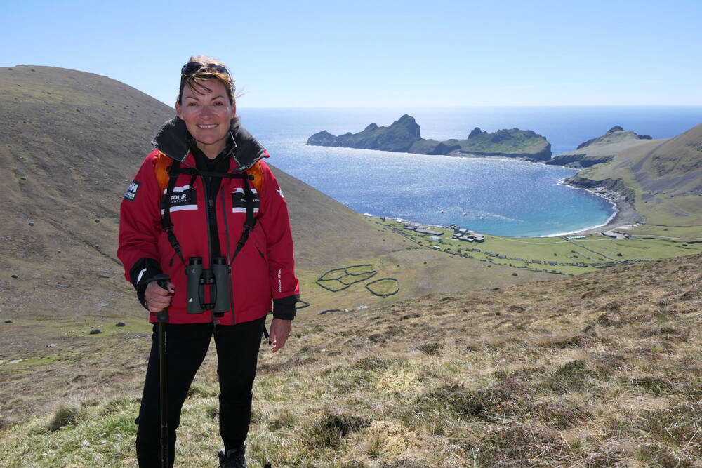Lorraine stands on a hillside with binoculars around her neck. In the background is the St Kilda coastline.