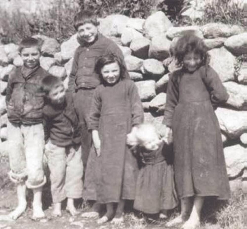 A black and white photograph of six children standing as a group in front of a stone wall. The three girls all wear long black dresses; the three bots wear black shirts with pale trousers, rolled up to the knees. They are all barefoot.
