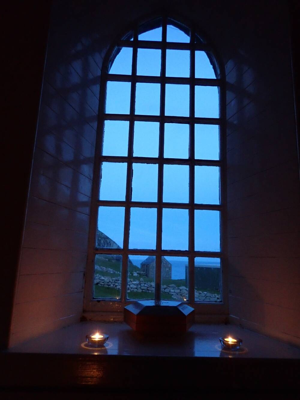 A view of a stone wall and hut from inside the church. It looks through a large window. Lit tealights flicker on the window sill.