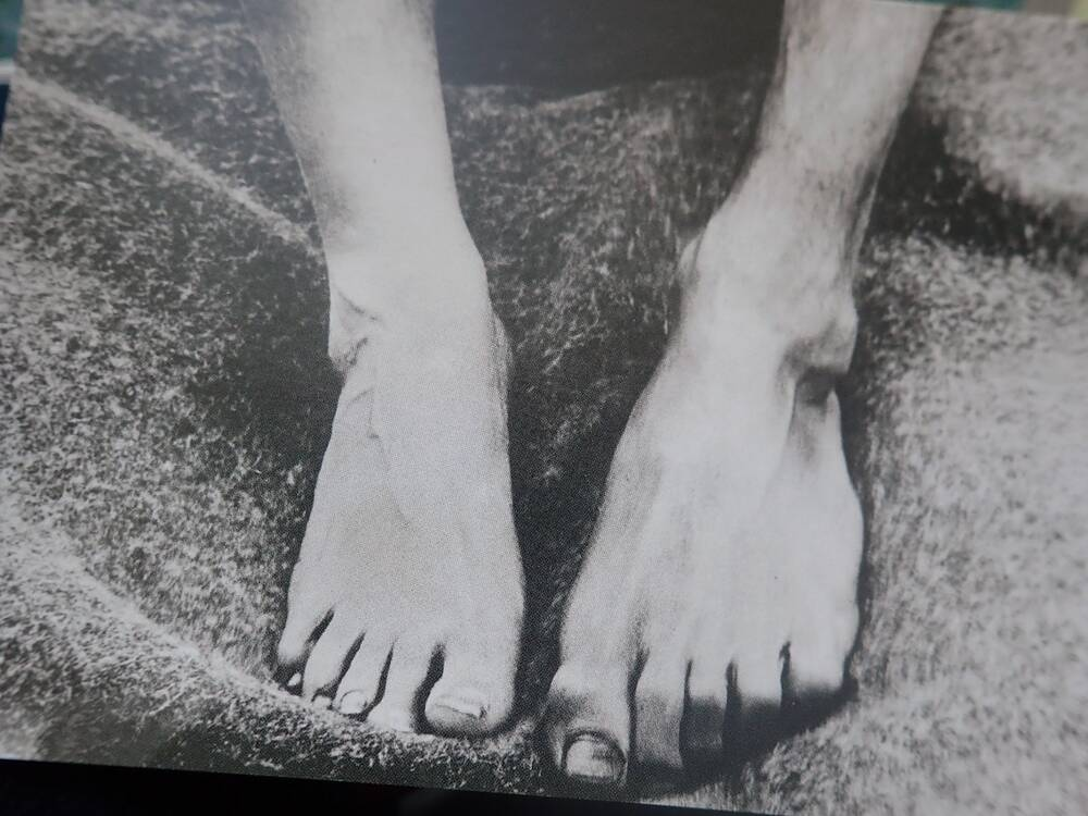 A black and white postcard showing two bare feet, one much larger than the other.