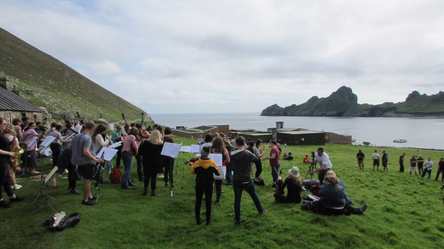A large orchestra plays in a field in front of a row of stone cottages on St Kilda. The photograph is taken from behind them and looks out to sea.