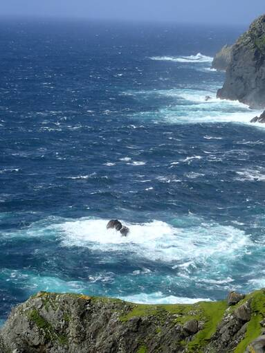 A view of the choppy sea, with waves crashing upon the rocks of the coastline.