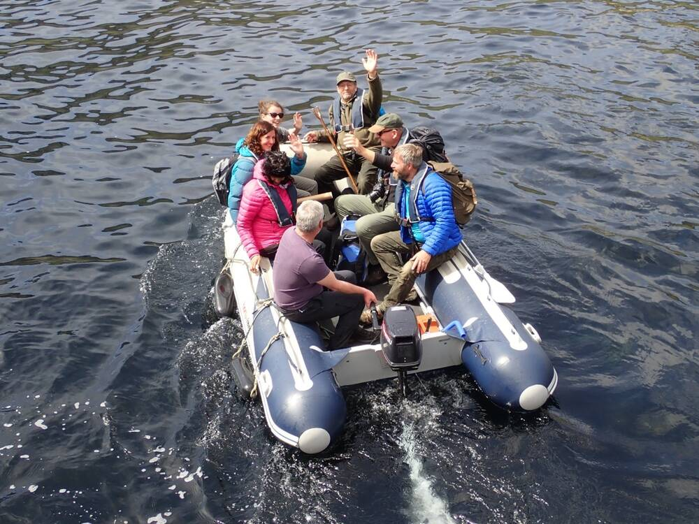 A group of people sit around the edge of a motorised dinghy as they head out to sea. Several of them are waving at the camera.