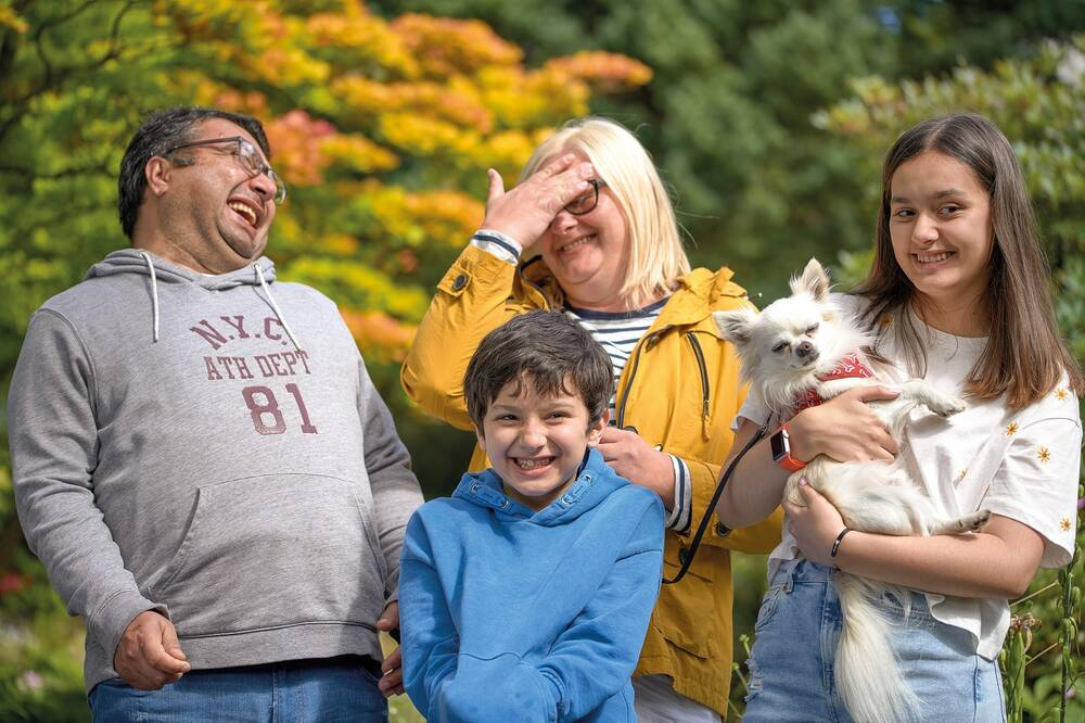A family group stand together, laughing. The dad on the left leans back slightly as he laughs. The mum in the middle holds one hand to her forehead, smiling. The girl on the right holds a small white dog in her arms. The young boy in the front grins with his hands in his hoodie pocket.