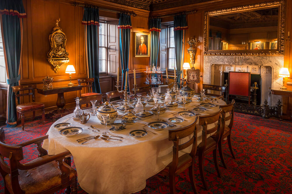 A formal dining room laid out at Brodie Castle. A long oval table is covered in white linen and set for dinner with 8 places. A large mirror hangs over the fireplace. Lamps set around the edges of the room provide a soft light.