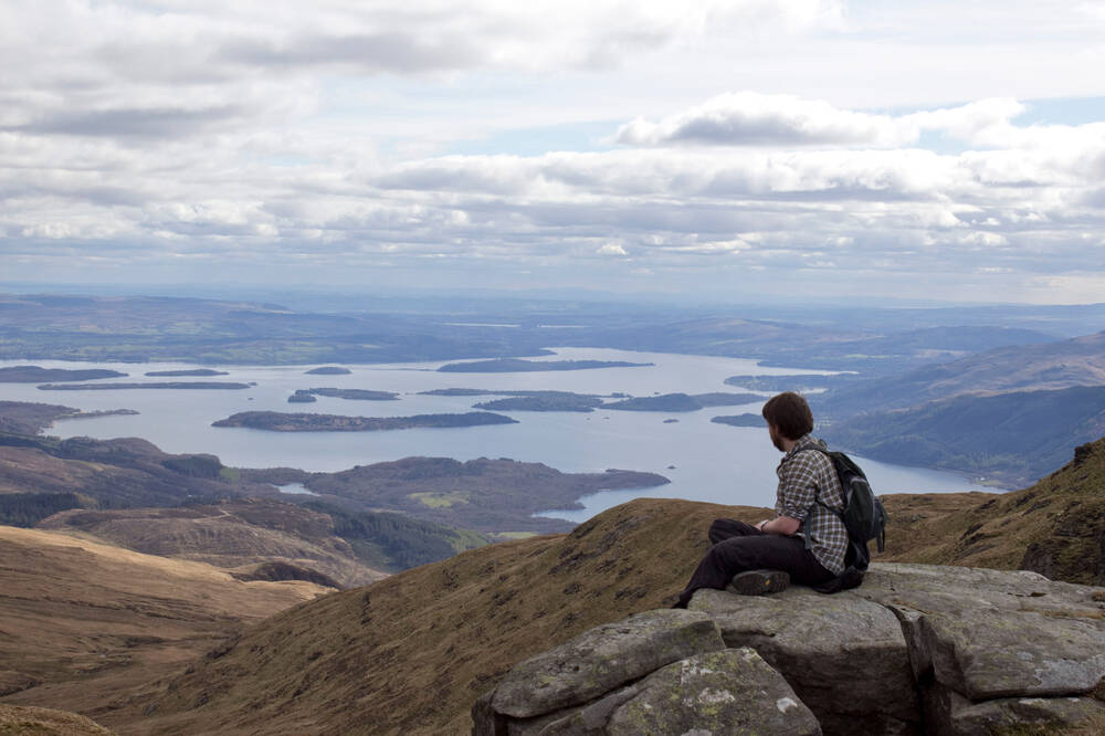 A walker enjoys the view from the top of Ben Lomond