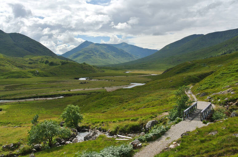 A view across the mountains of West Affric. There is a path with a wooden footpath to the right of the image, leading through the glen. The bridge crosses a hillside burn, which feeds into the river to the left of the image.
