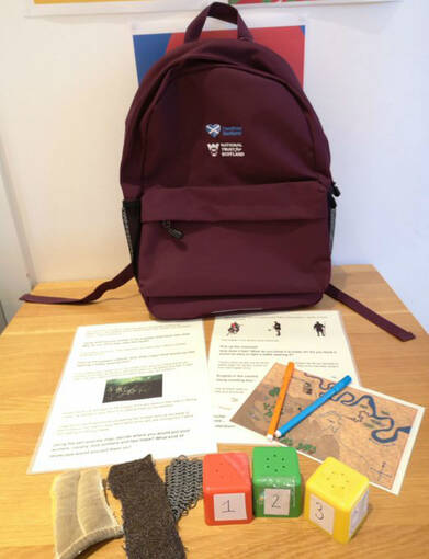 A backpack on a table, with its contents displayed in front of it, including acitivity sheets, pencils and sensory material