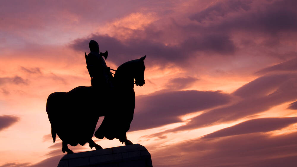 The statue of Robert the Bruce on a horse, silhouetted against a red and purple sky.