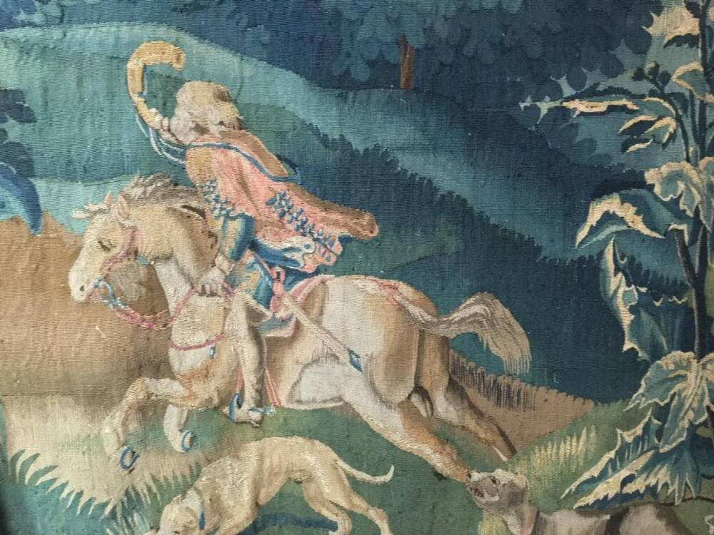 Detail from a tapestry showing a man riding a horse, blowing on a horn.