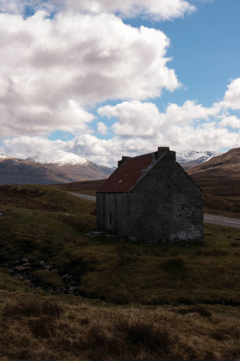 An abandoned bothy stands on a hillside with snow-capped mountains in the distance.
