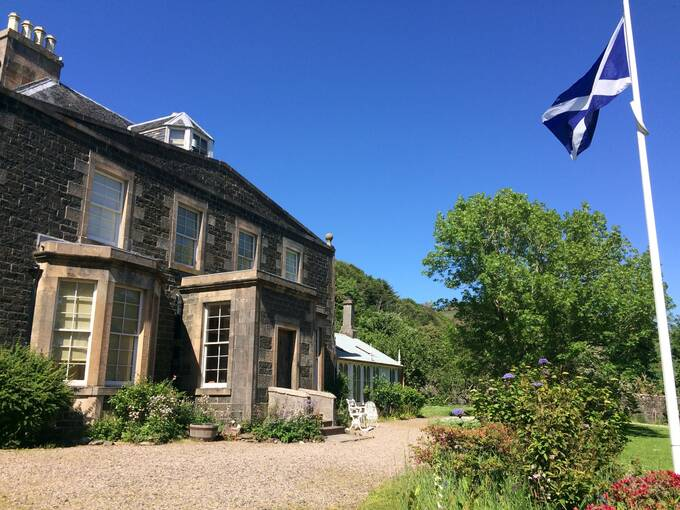 A large stone detached house on a sunny day, with a flagpole in front of it flying the Saltire.