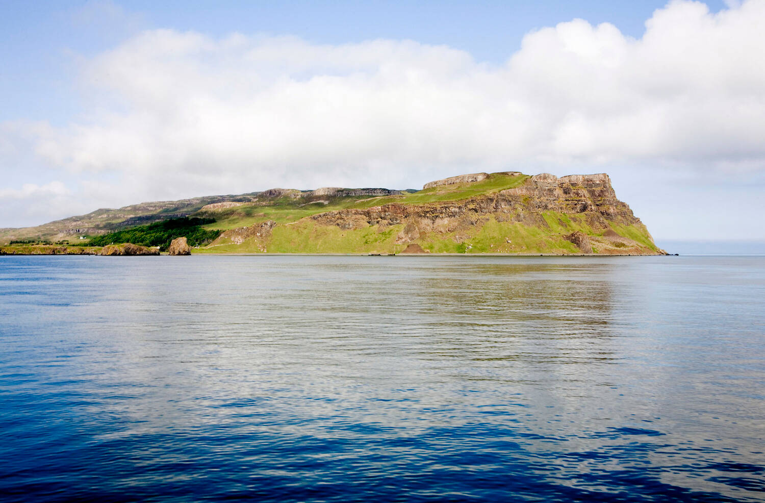 Canna seen from the sea on a calm sunny day. The island is reflected in the smooth water.