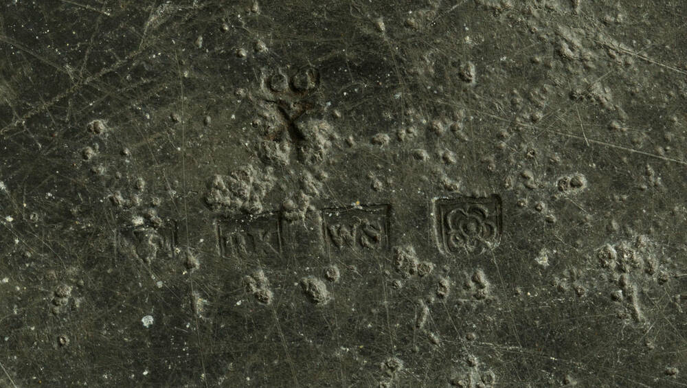 Detail of the stamps (a thistle, RK, WS and a rose) on the underside of a pewter plate from Culross