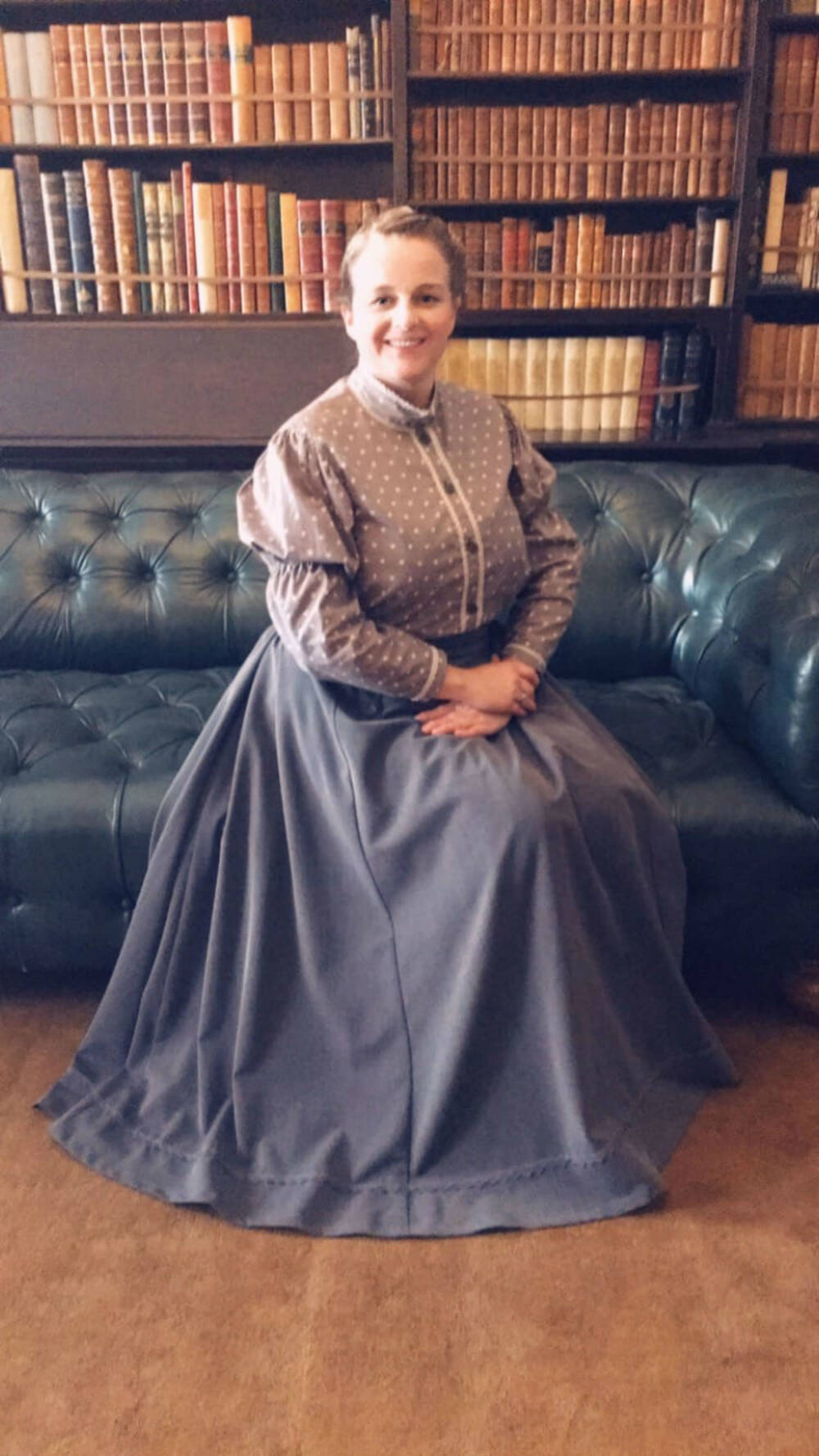 Woman in period costume sitting on a chesterfield sofa in front of a bookcase