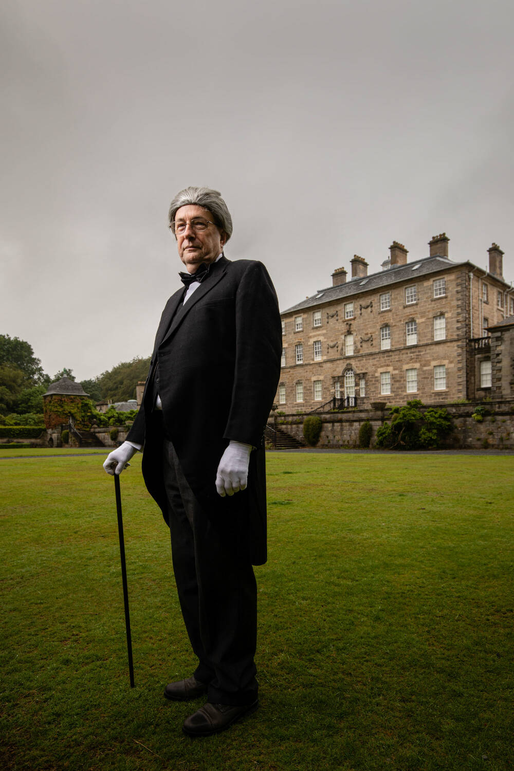 A man dressed as a butler in front of a stately home