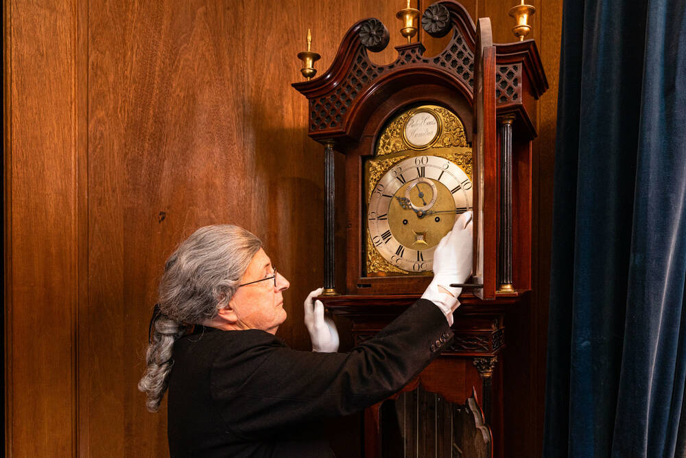A man in period costume with a grey wig winding a clock