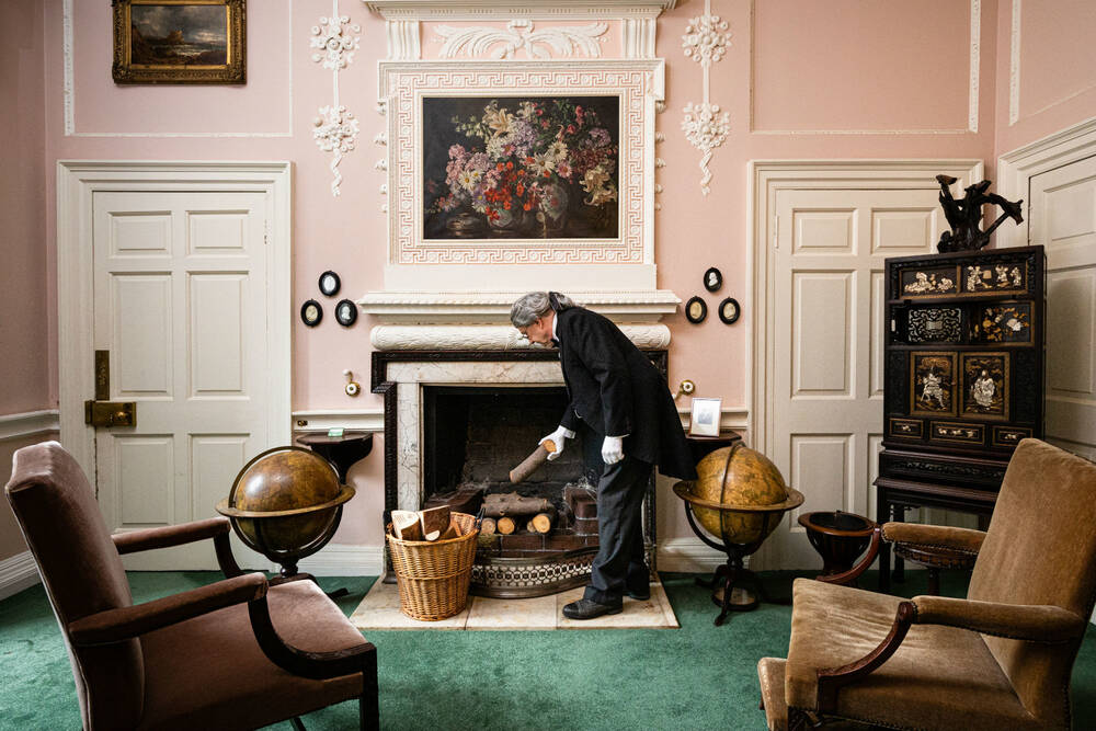 A man in period costume adding logs to a fireplace