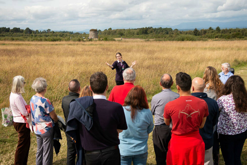 Guide showing a group of people around the Culloden Battlefield