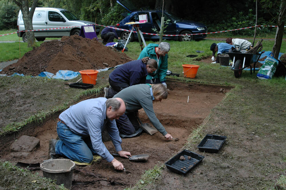 Four people kneel in a shallow rectangular trench cut in a lawn. They use small trowels to scrape the earth in front of them. A large mound of earth is behind them. Two cars are parked in the background.
