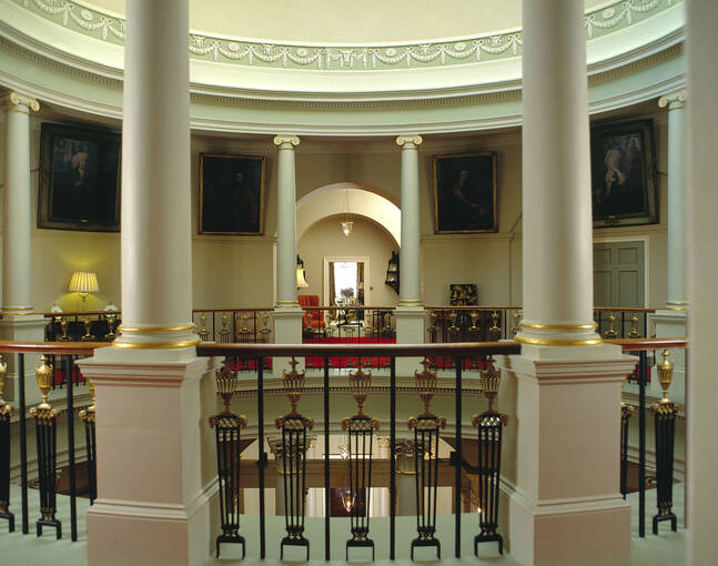 A view looking between two columns on a landing of the Oval Staircase. Framed portraits hang on the walls.