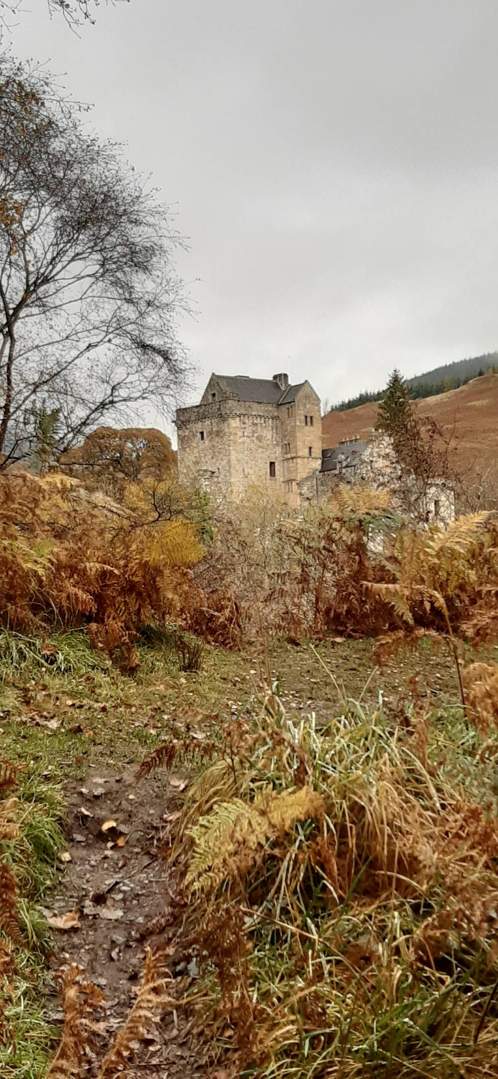 A ruined castle sits high on a hill. There is a rough path leading up to it; the bracken on either side of the path is turning orange and brown as it is autumn.