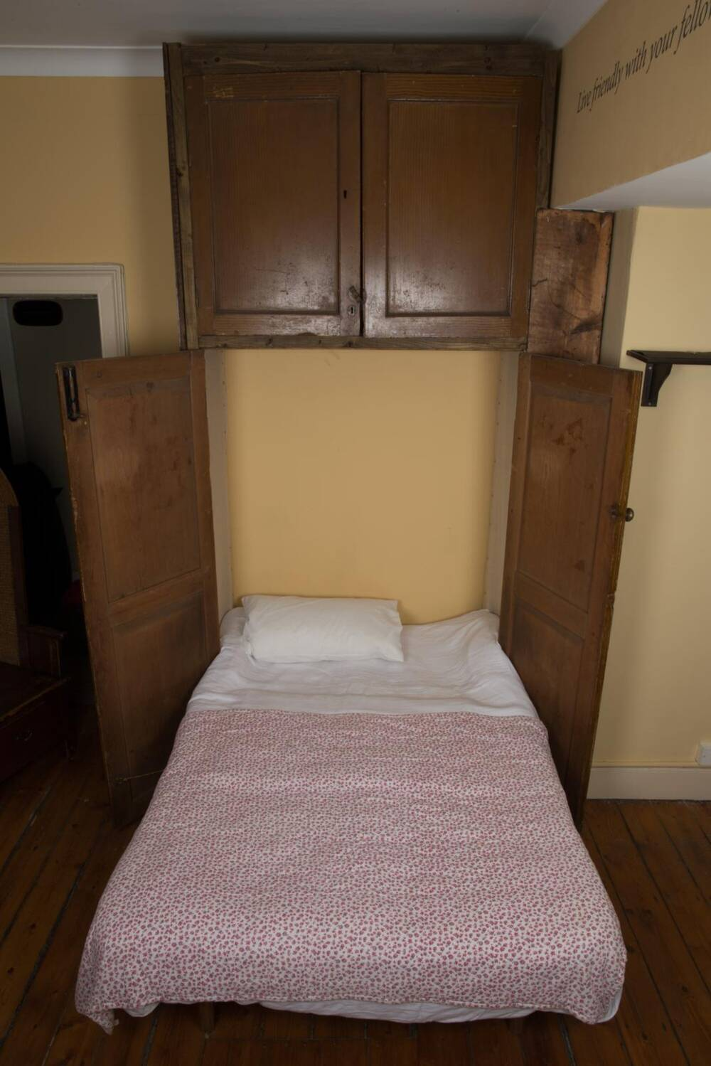 A pull-down bed, which is normally kept hidden behind a large wooden cupboard.