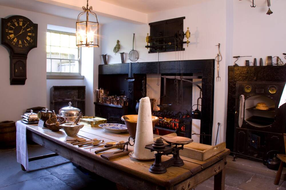 A restored Georgian kitchen, with a large black range and a wooden table in the centre of the room with kitchen implements on it.