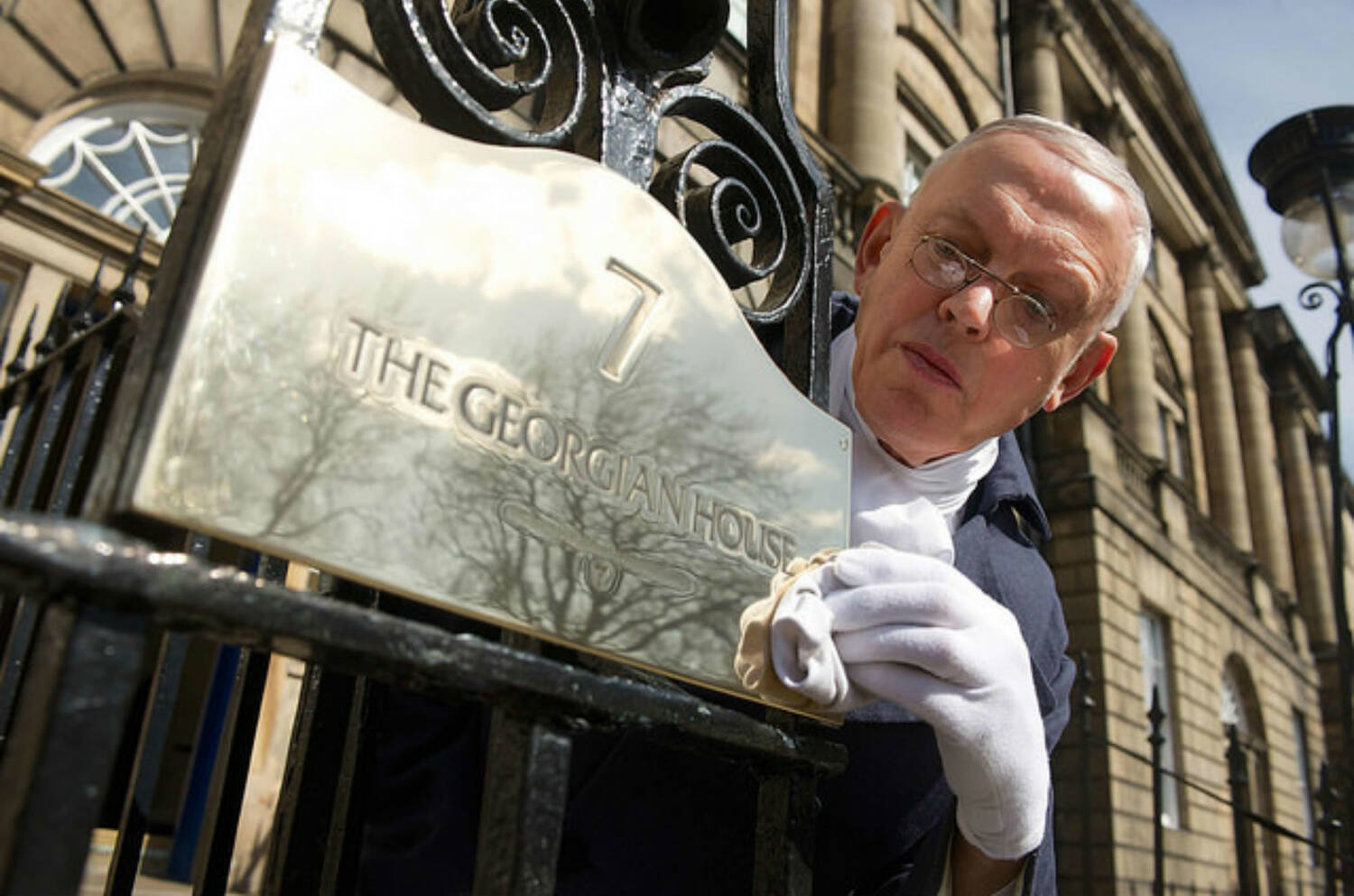 A man with white cotton gloves is polishing a brass plaque which says 7, The Georgian House.