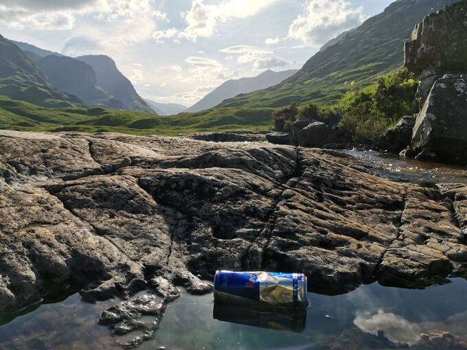 A drinks can left in a stream in a mountainous landscape.