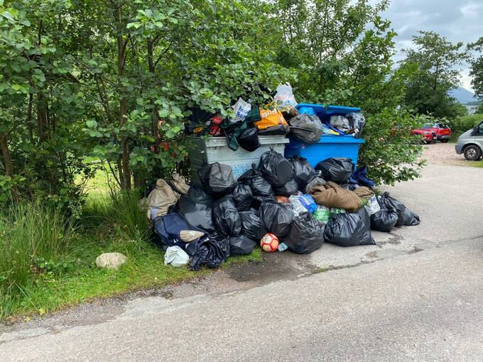 A large blue rubbish bin at a roadside overflowing with black rubbish sacks and other rubbish.