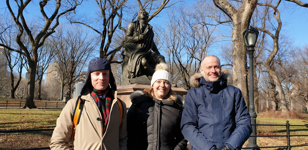 Three people stand in front of a statue of Robert Burns in Central Park, New York