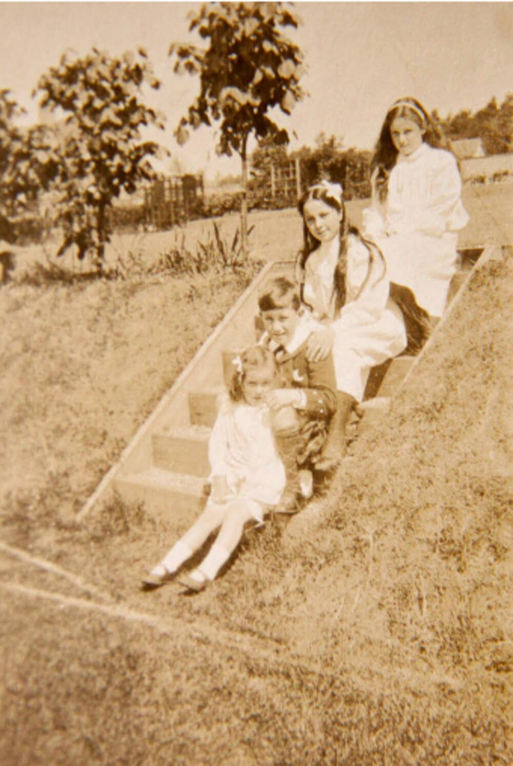 Black and white photograph of three girls and a boy sitting on some stone steps in a garden.