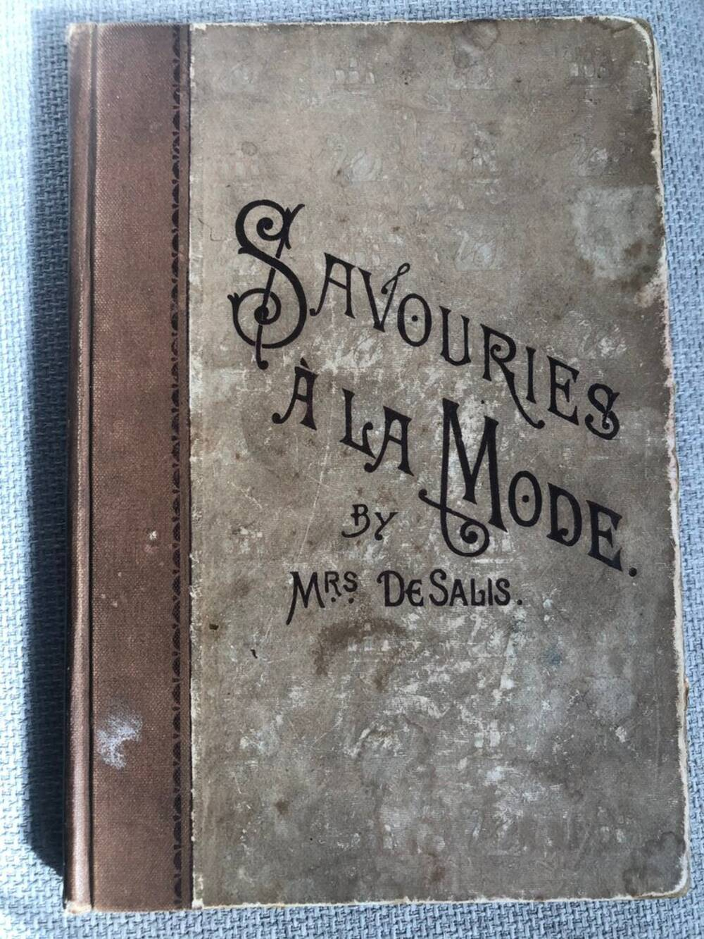 A battered cover of an old cookbook: 'Savouries a la mode' by Mrs De Salis.
