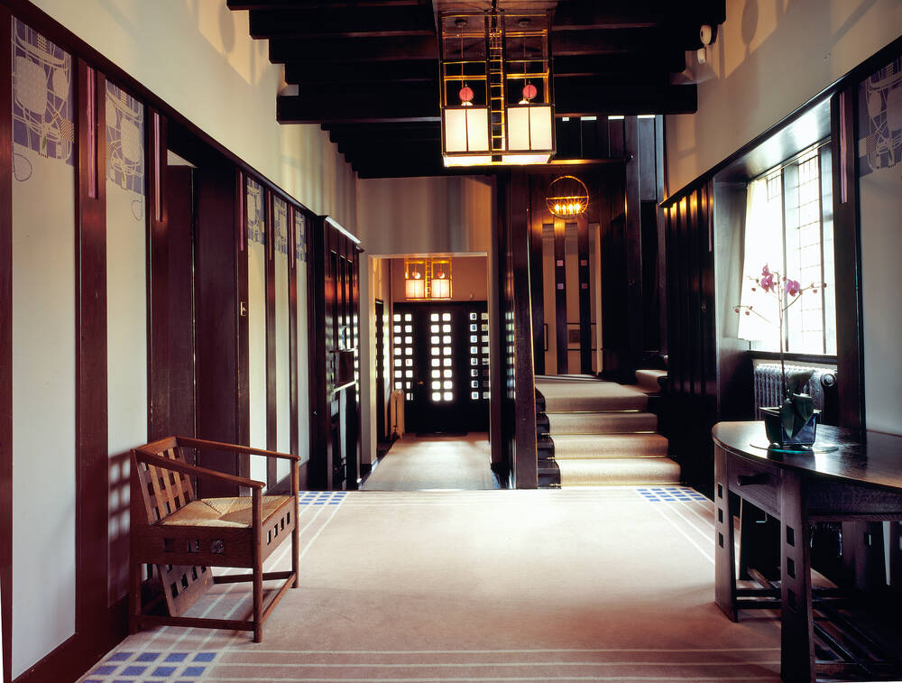 A view of the hall inside the Hill House. Cream carpets run the length, with a Mackintosh wooden chair to the left and sidetable to the right.