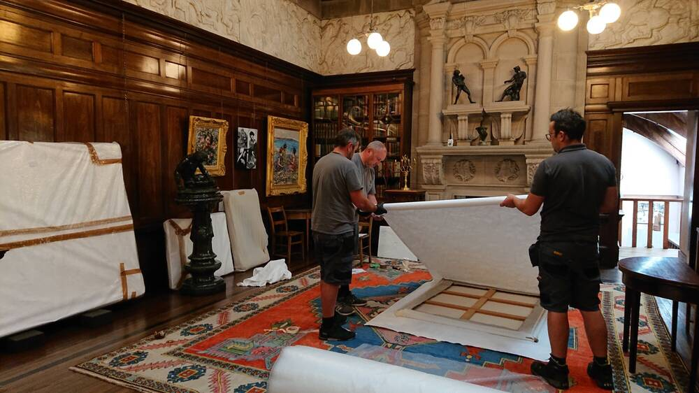 Three men wrapping a painting in white material. The painting is lying on the floor of a gallery, with other paintings and statues on the walls.