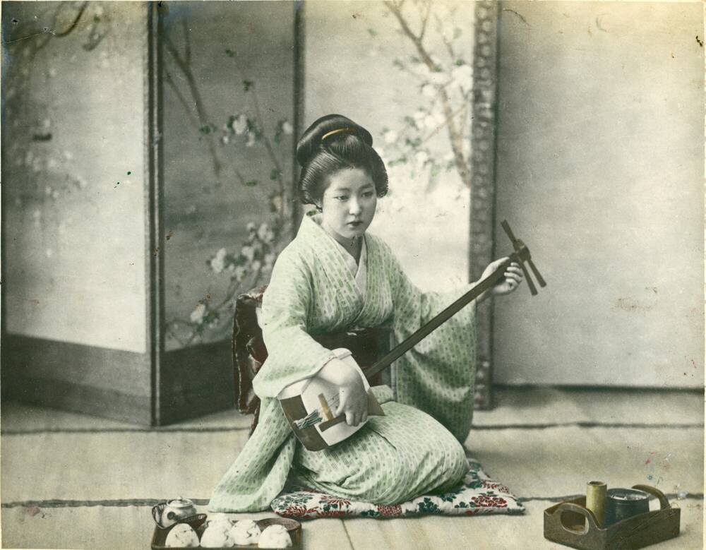 Delicately coloured photo of a Japanese lady playing a shamisen in front of a screen decorated with cherry blossom.