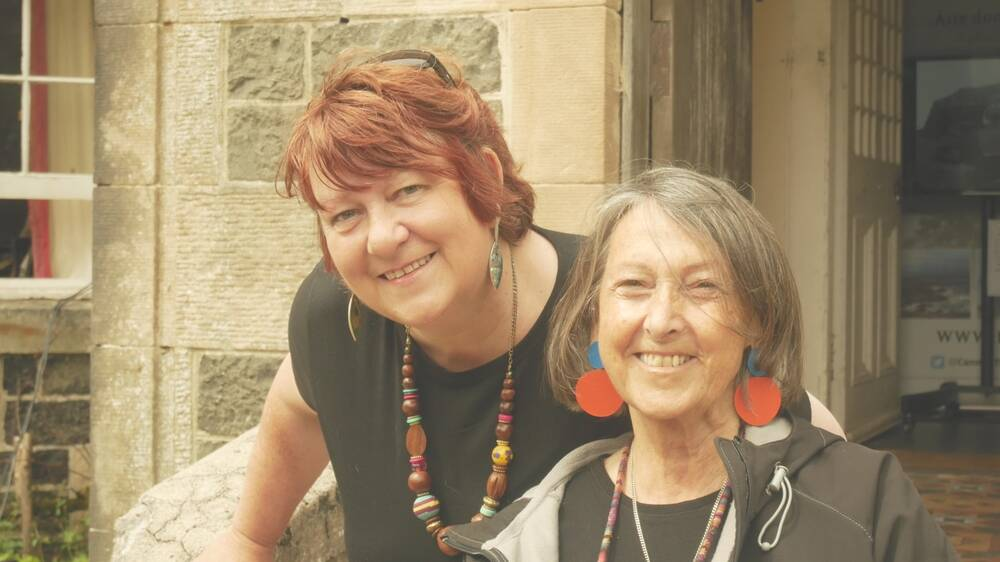 Colour photograph of the head and shoulders of two women outside a stone house.