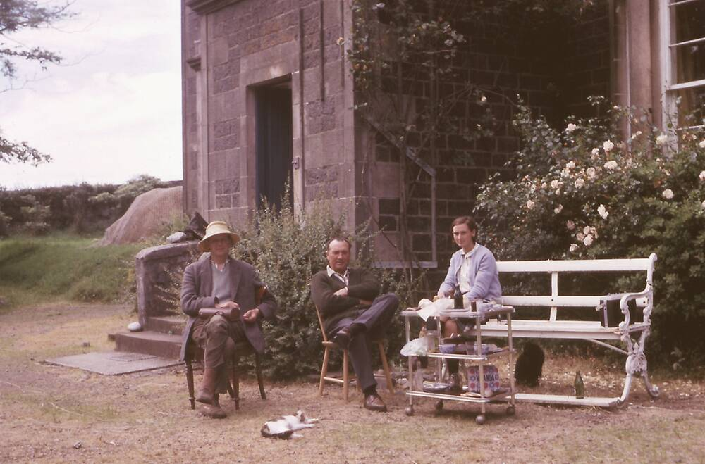 Colour photograph of a girl and two men sitting outside a grand stone house.