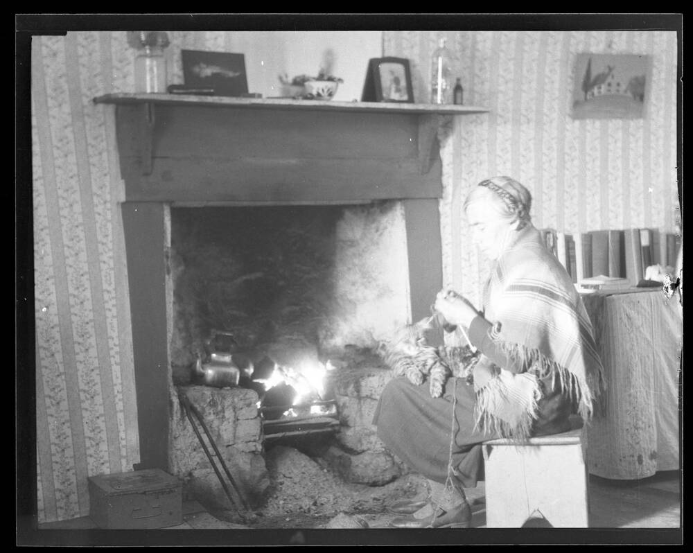 A black and white photograph of an older woman knitting beside a fire place with a tabby cat on her lap.