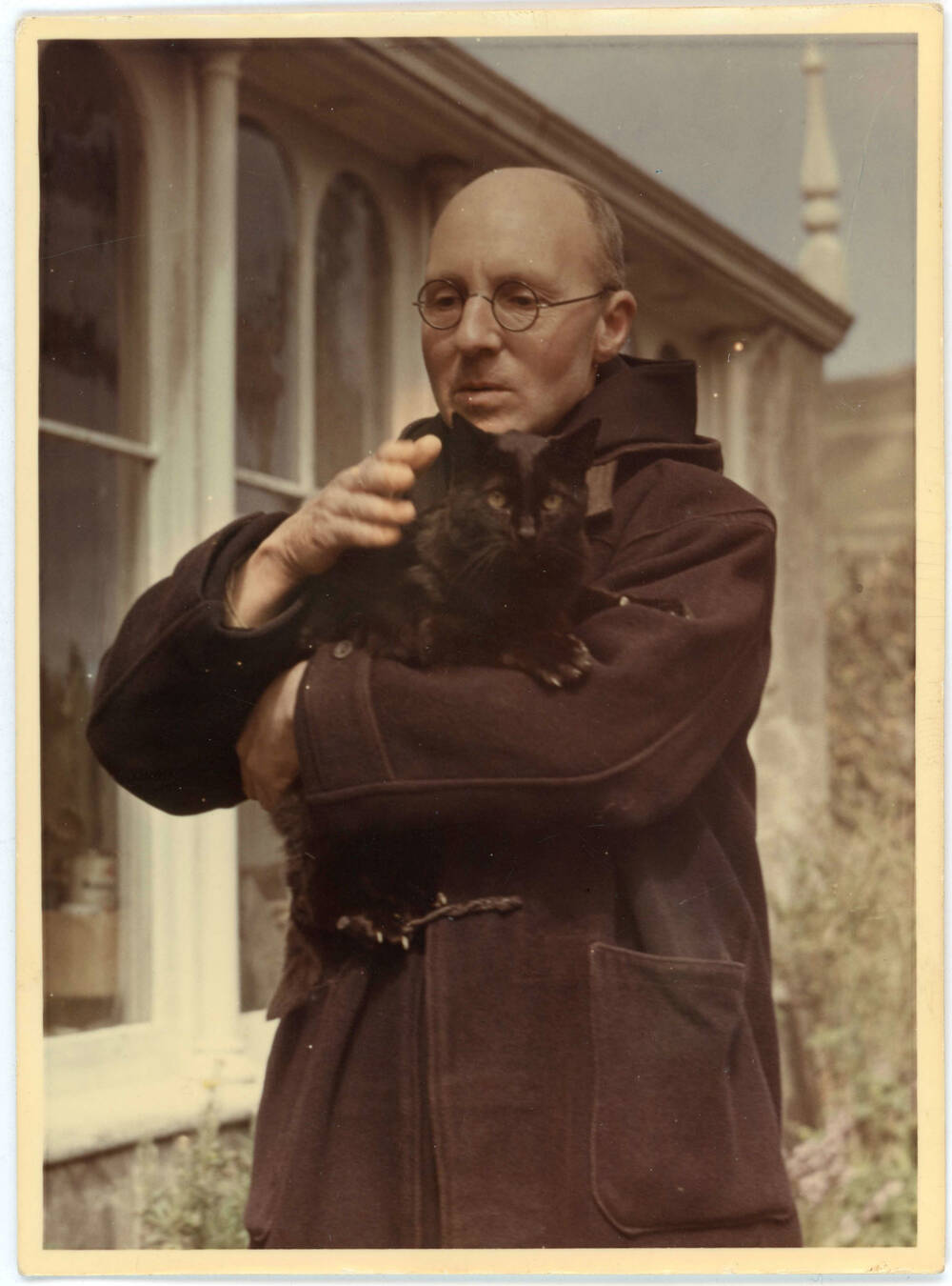 A colour photograph of a priest holding a black cat with green eyes. The priest is bald and wears glasses and a black coat.