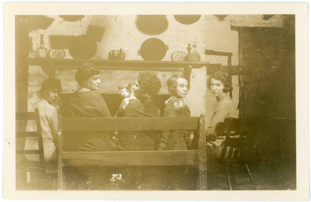 A black and white photograph of five women sitting in front of a fireplace. At the centre, one of them is holding a cat.