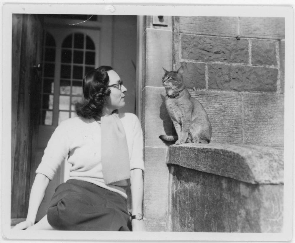 A black and white photograph a woman sitting on the front steps of a house looking at a cat which sits to her left.