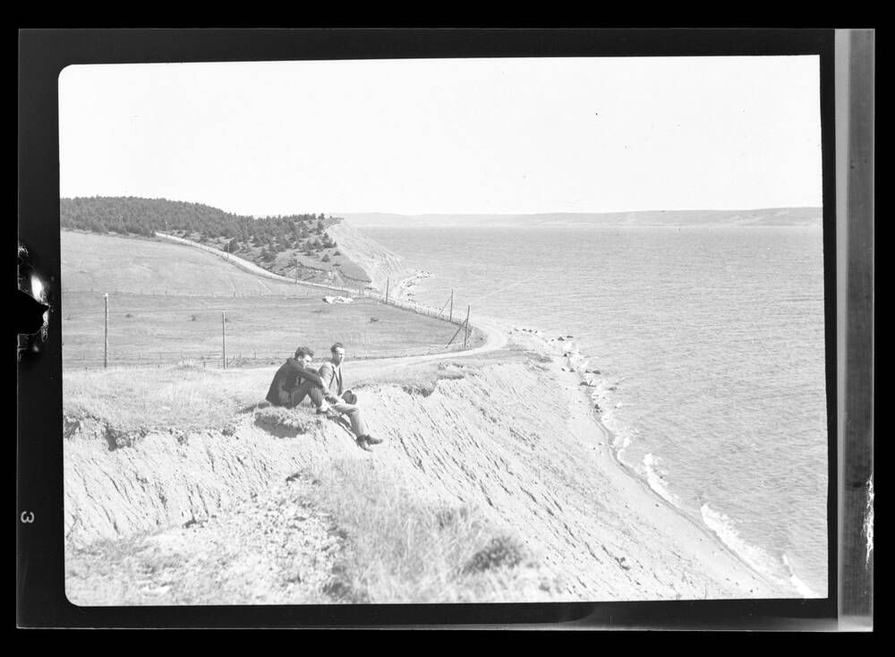 Two men sitting at the edge of a cliff by the sea