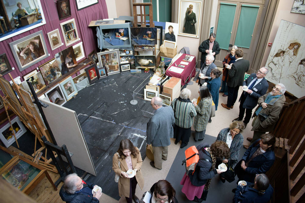 A crowd standing in the studio of painter E A Hornel at Broughton House. Paintings by a contemporary artist are on display.