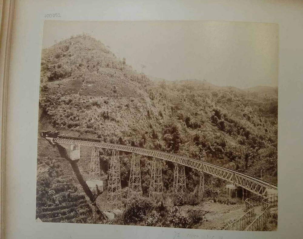 A black and white photo of a train crossing an iron-lattice viaduct, with jungle-covered hills in the background.
