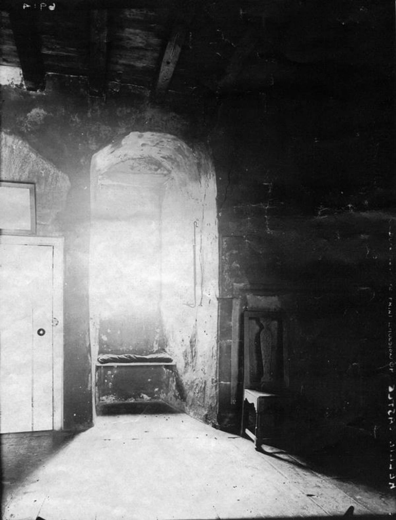 A black and white photograph of a window in the wall of a stone tower. Light streams through the window, illuminating the room.