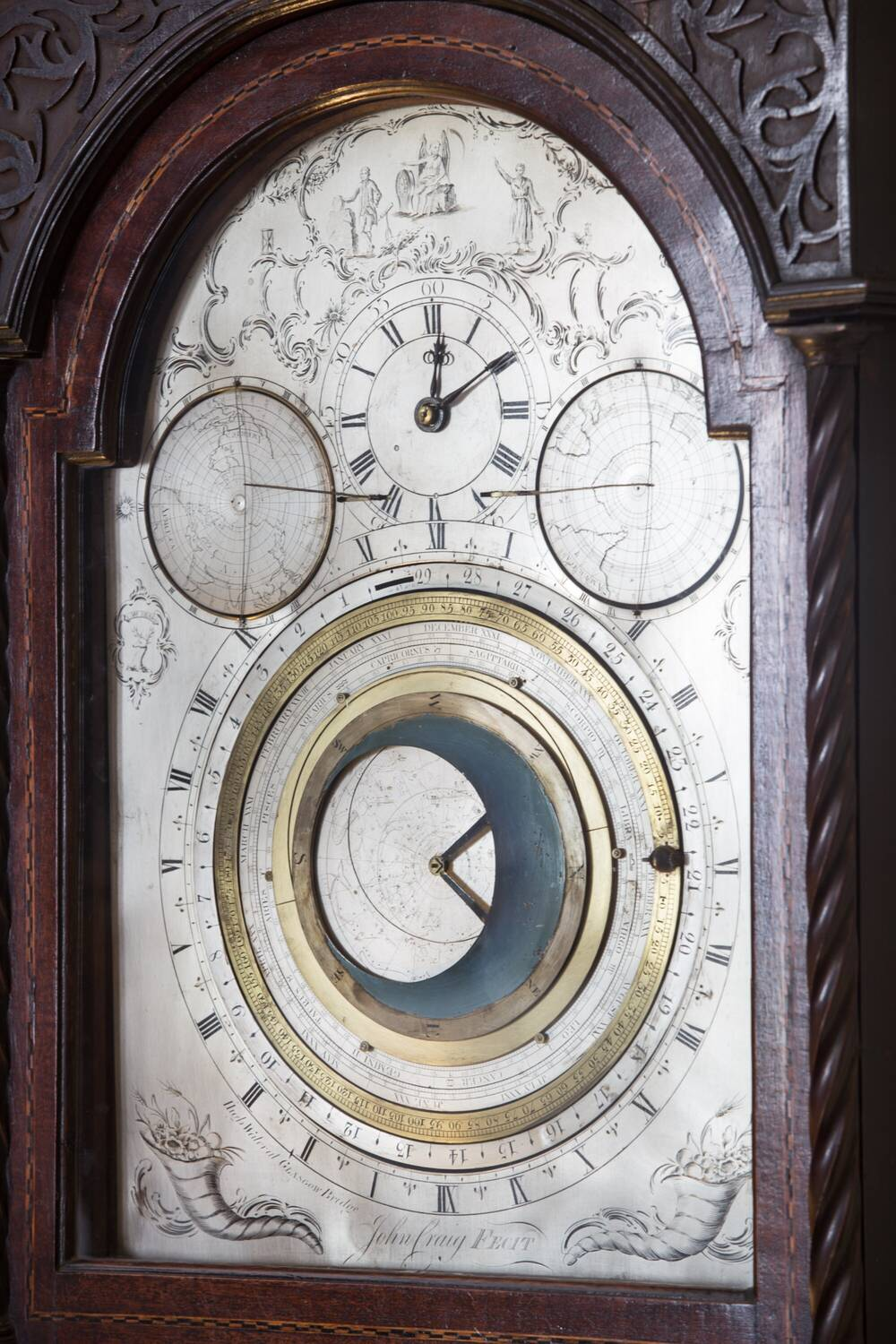 An ornate clock in a dark wood casing. As well as the clock face for telling the time, there are other faces showing seasons and also the northern and southern hemispheres