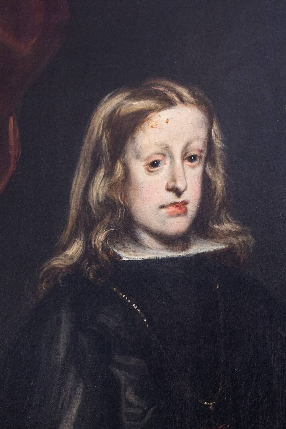 Portrait of a boy with long brown hair. He has an elongated face with a pronounced jaw.