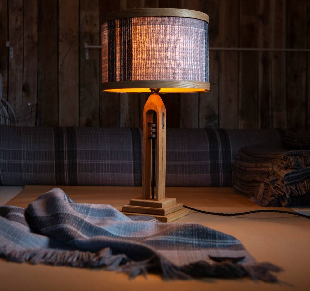 A lit lamp with a shuttle for a base. Tartan cloth lies in front of it.